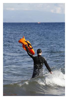 Rettungsschwimmer gibt Navigationshilfe auf Lesbos. Im Hintergrund Assos, Tuerkei